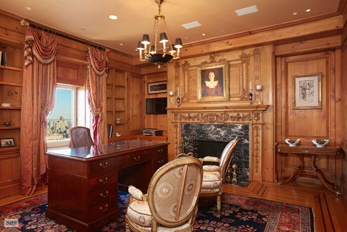 The paneled library with fireplace.