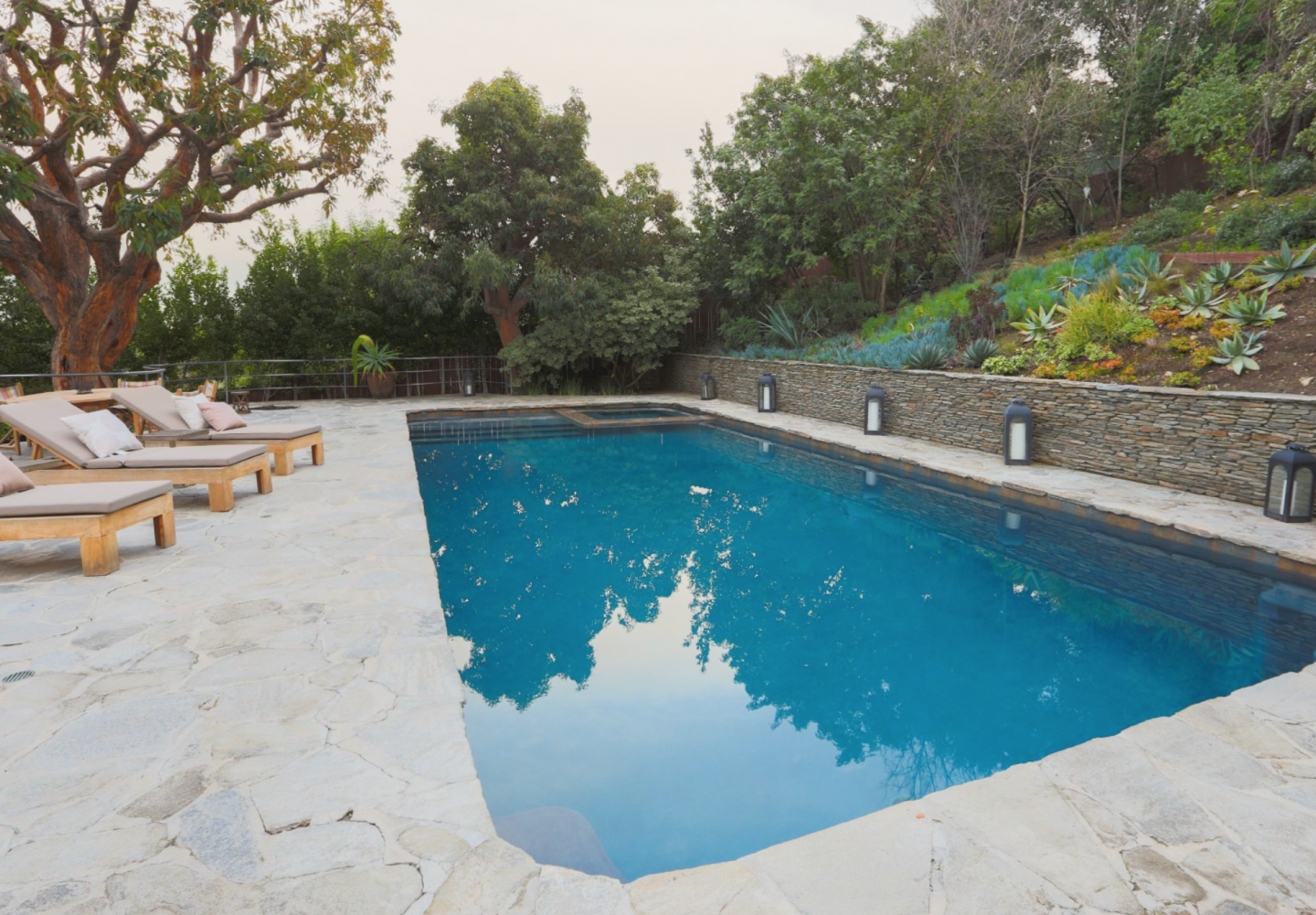 Saltwater pool and deck with privately-tiered surroundings.