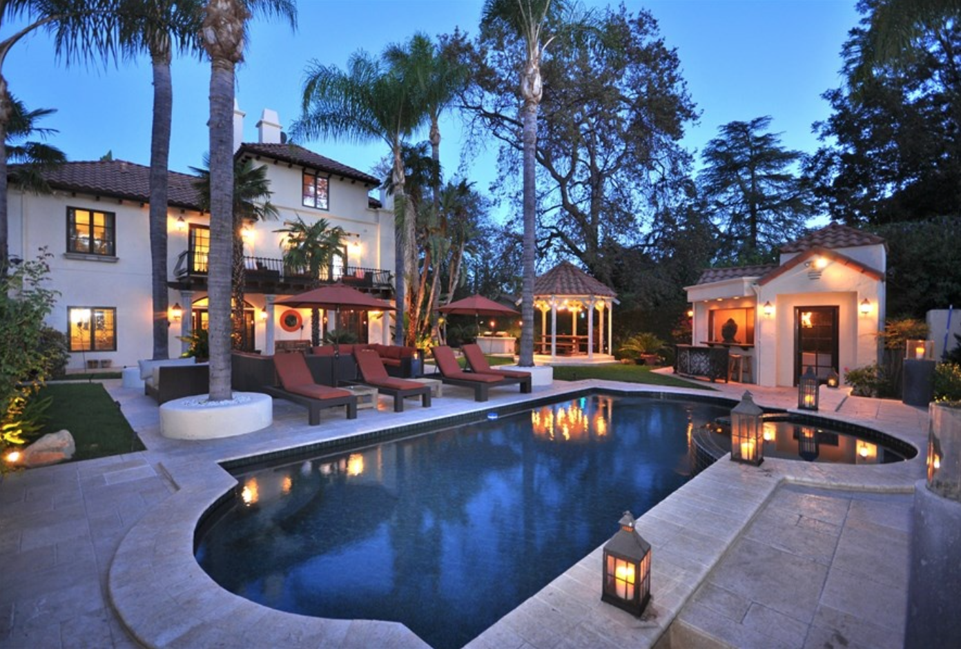 The Encino estate has a private, resort-style backyard with a pool and palm trees.