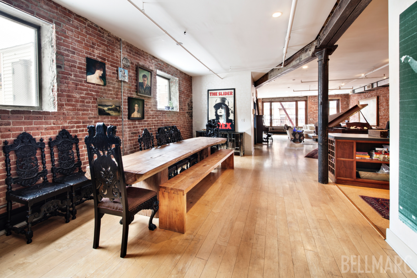 The loft boasts exposed brick walls, original iron columns,  and hardwood floors.