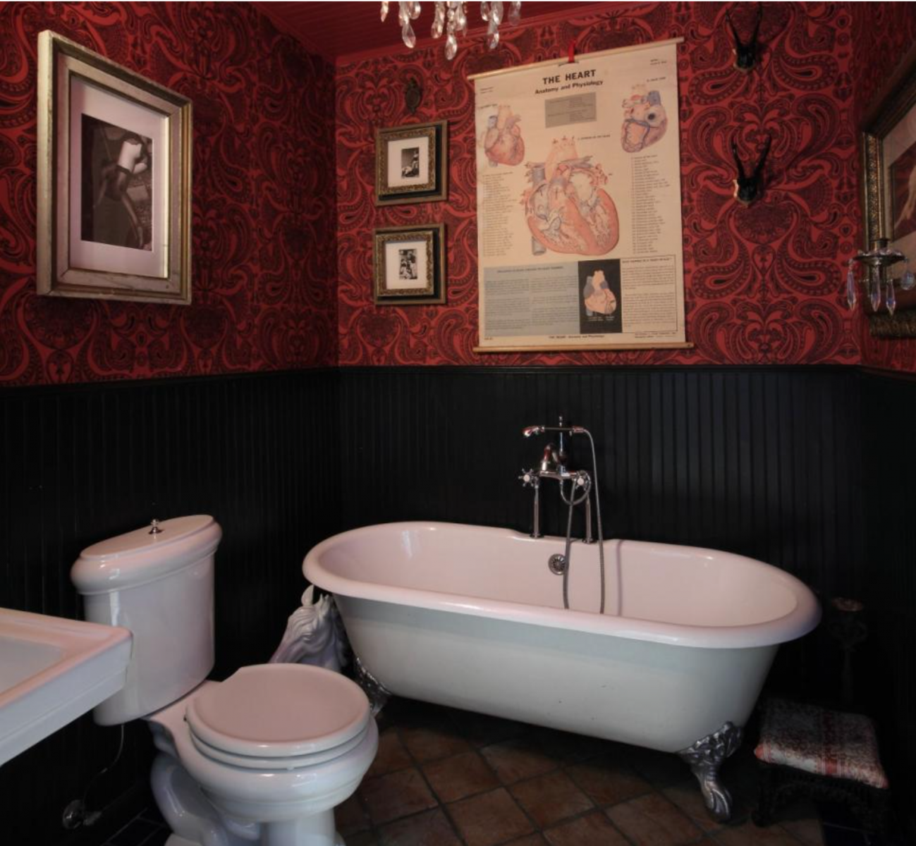 The apartment has two bathrooms, one of which resembles a Moulin Rouge set with deep red hues and a chandelier.