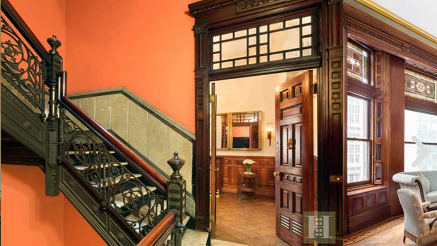 Orange hues complement the ornate wrought-iron staircase and carved mahogany pocket doors.