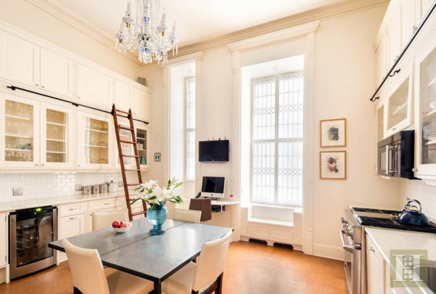 The duplex boasts 14-foot ceilings and features sliding ladders for convenience.