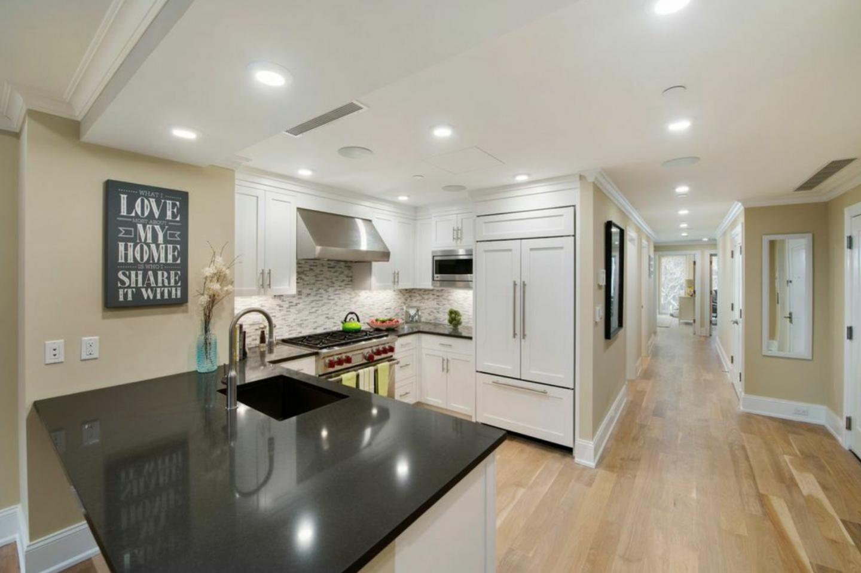The chef's kitchen features a breakfast bar, Caesarstone countertops,  and Subzero refrigerator.
