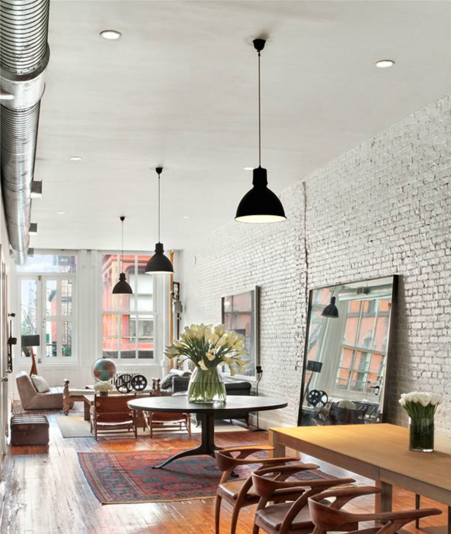 The home features exposed brick walls, original hardwood floors and ceilings that soar more than 13 feet high.