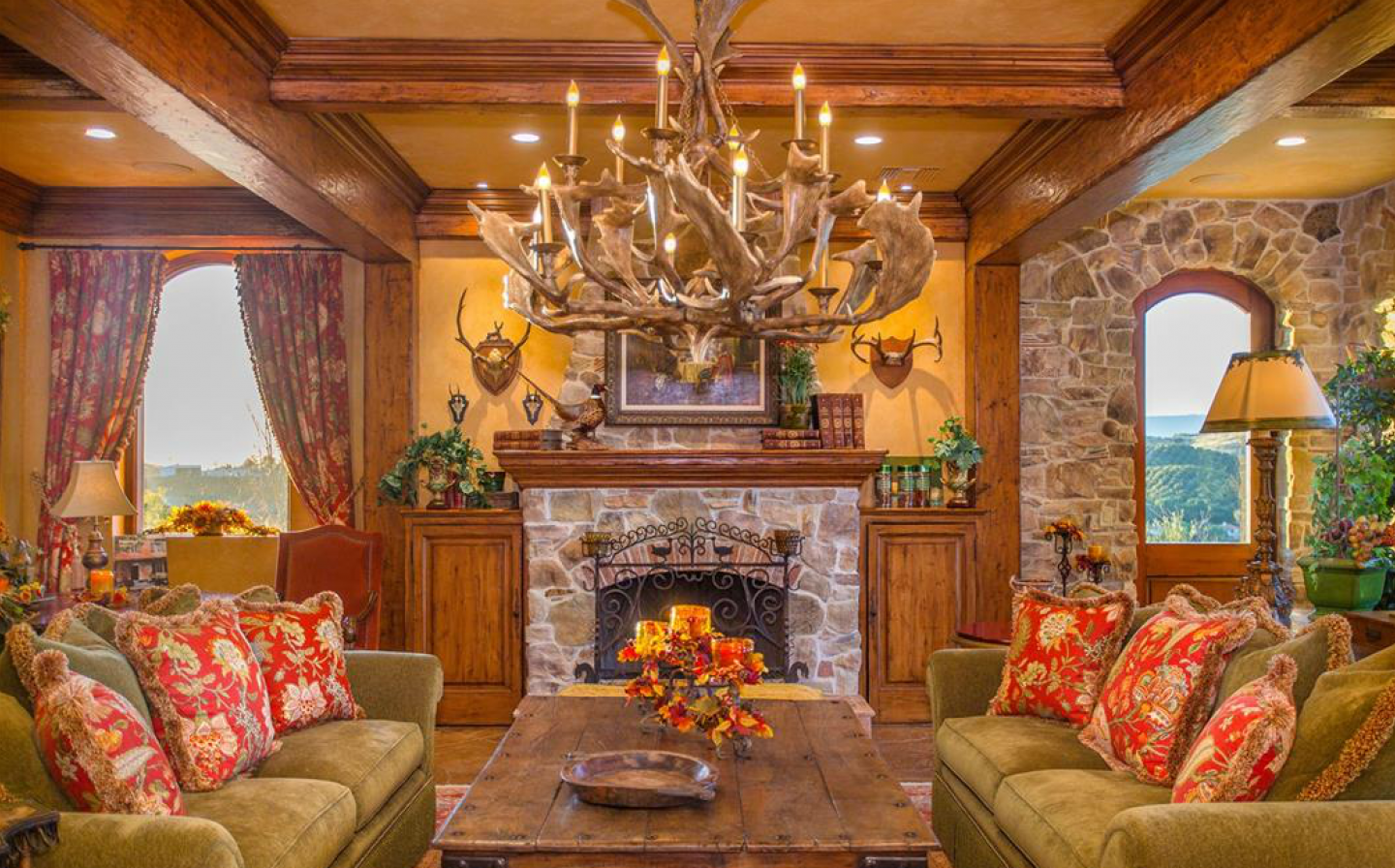 Fireplace and antler chandelier mix western and Tuscan flavors