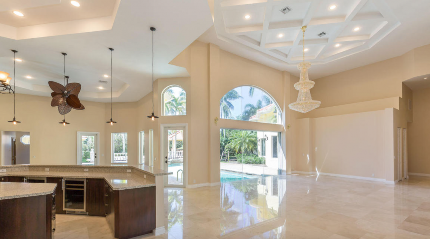 A grand entrance boasts two crystal chandeliers, huge impact windows and 21-foot ceilings.