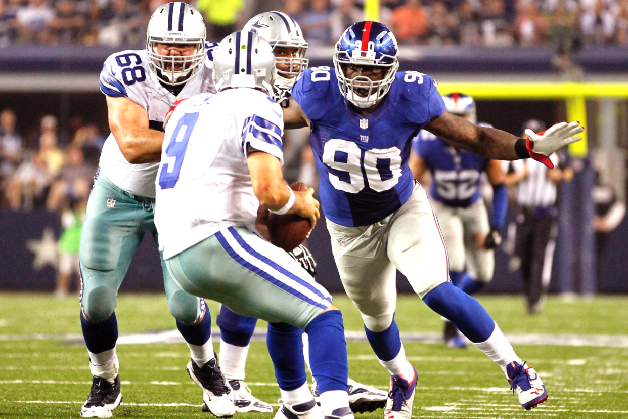 Jason Pierre-Paul at his office, about to sack Dallas Cowboys quarterback Tony Romo.