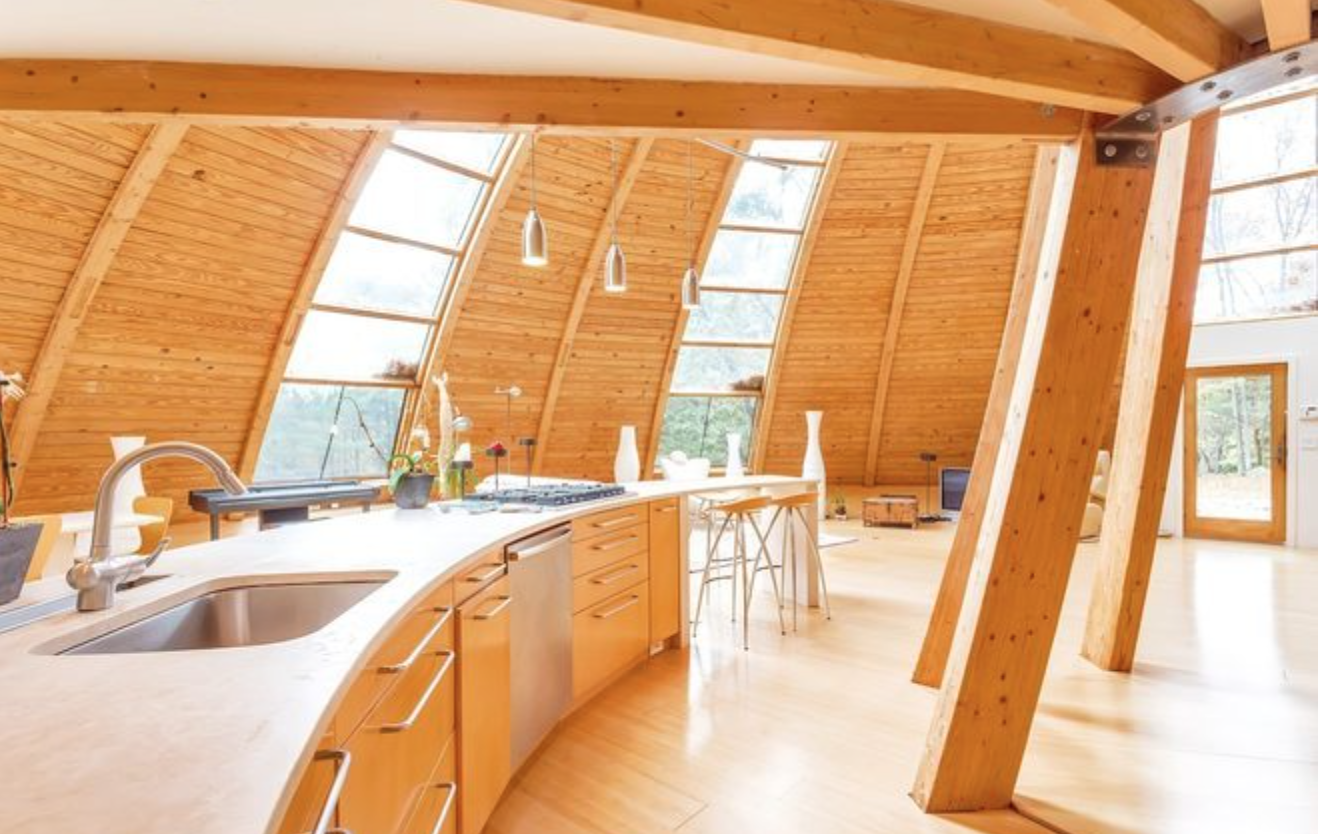 The house showcases curved windows with an open, wall-free floor plan.