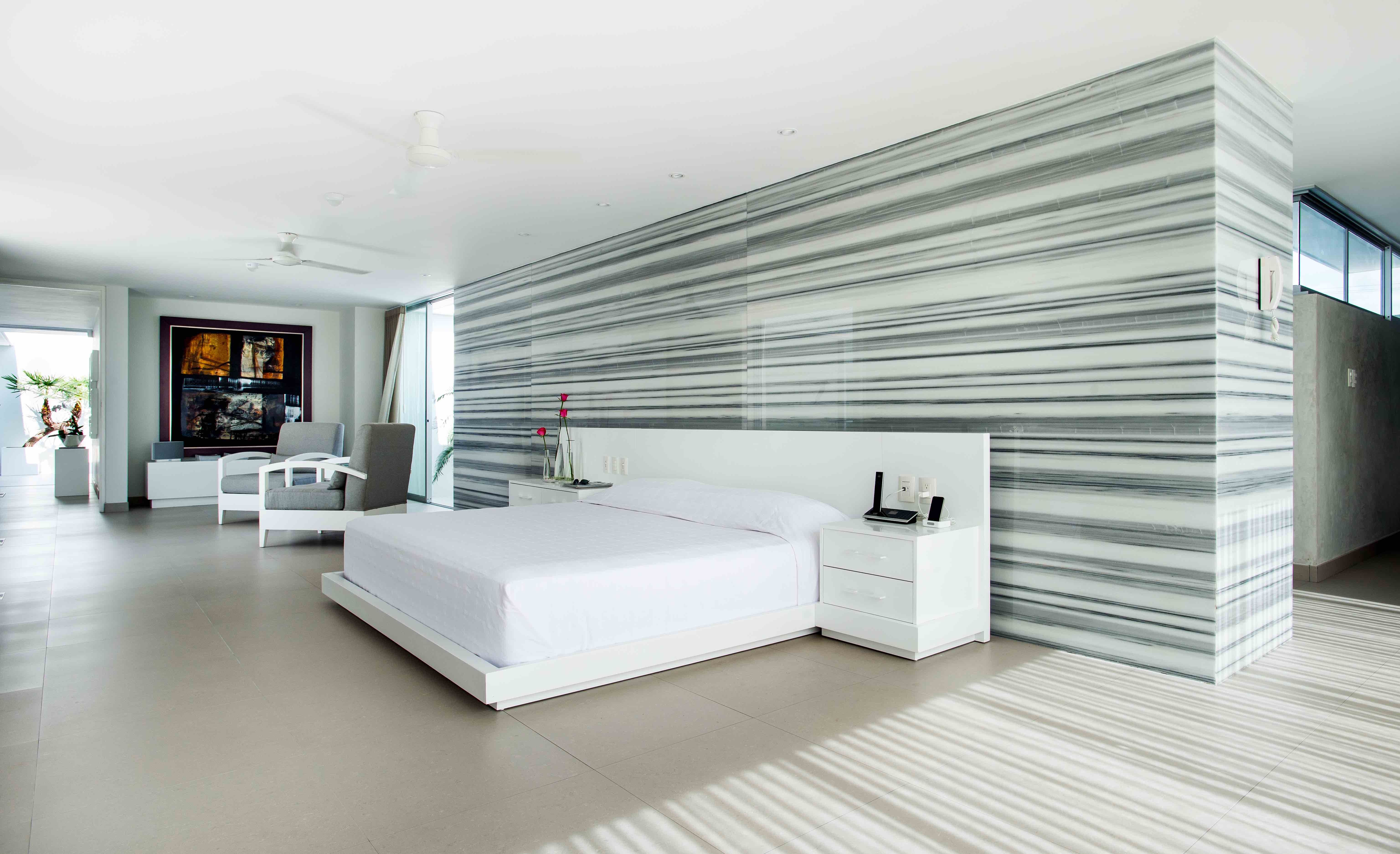 The master bedroom features walls of grey and white marble and sand-colored stone floors