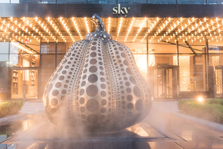 An infinity loop motor court circles an enormous ornamental bronze pumpkin, dotted in black stone––an original work of art by illustrious Japanese artist Yayoi Kusama that was commissioned for Sky