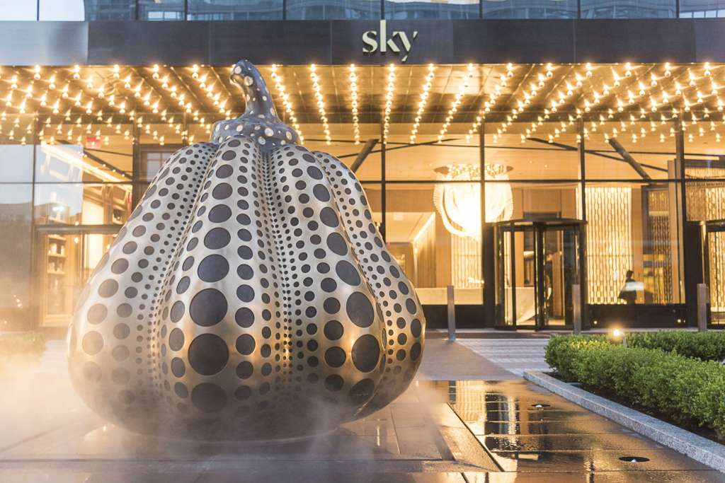 At the forefront of the building, an infinity loop motor court circles an enormous ornamental bronze pumpkin, dotted in black stone––an original work of art by illustrious Japanese artist Yayoi Kusama that was commissioned for Sky