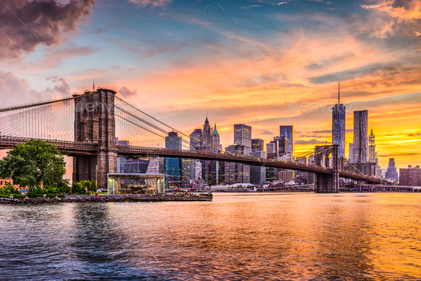 New York City Skyline on the East River with Brooklyn Bridge at sunset.