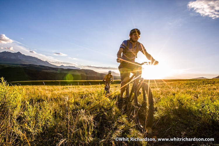 A man and a woman riding mountain bikes through a field.